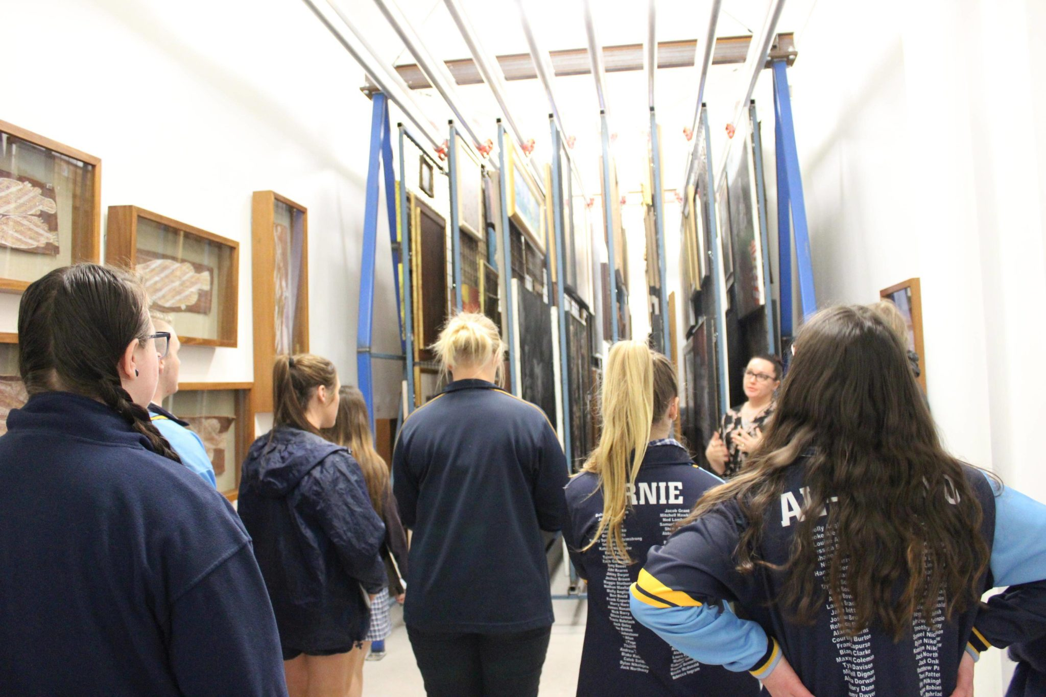 Image credit: Latrobe Regional Gallery's Education and Public Programs Officer Nicole Brindley showing students through the back of house painting storage areas.