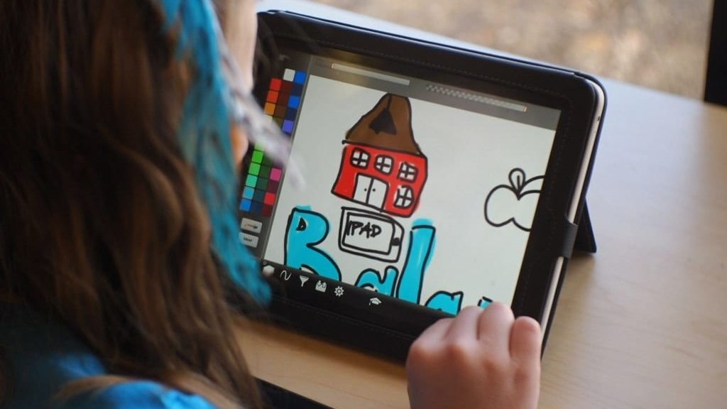 Child using a tablet to create an artwork